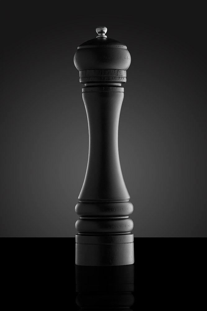 Rasnita de piper neagra din lemn pe fundal negru si cu reflexie