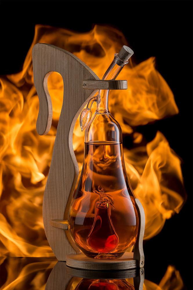 Concept sticla de tuica in forma de para pe fundal negru cu foc Transilvania Glass